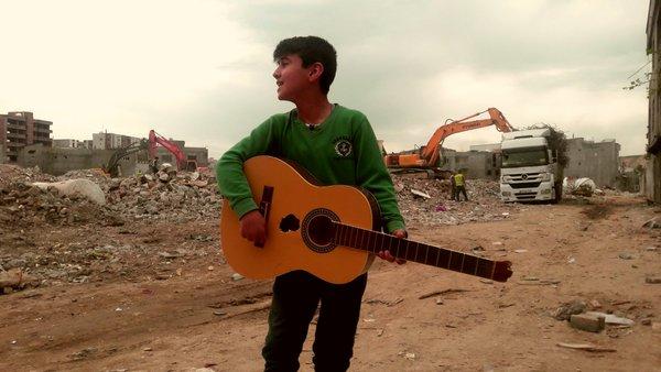 """Aylar süre ablukadan sonra Suriye'ye dönmüş Cizre'de, evlerinin enkazından kurtardığı kırık gitarıyla """"Li Qamişlo"""" şarkısını söyleyen çocuktur umut."""
